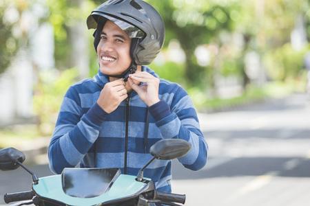 街の通りで彼のバイクのヘルメットを固定する幸せな男