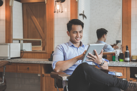 Experto en peluquero seguro Hombre joven con tablet pc sonriendo mientras estaba sentado en la barbería Foto de archivo - 74823466