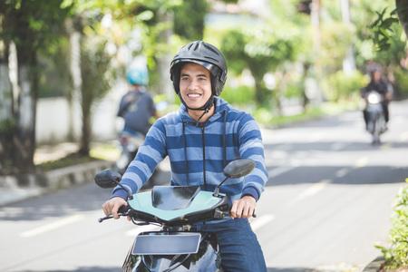 portrait de l'homme asiatique heureux à cheval sur la moto dans la rue de la ville