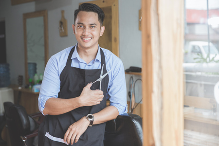 Confident barber expert. Young man looking at camera and smiling standing at barbershop Stock Photo