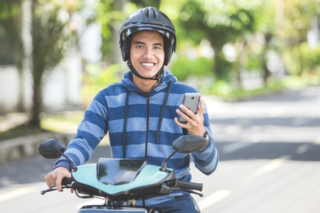 portrait of happy asian man using mobile phone while riding on motorbike in city street