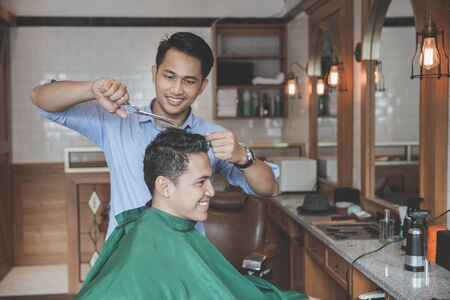 Cheerful young man getting haircut by hairdresser at barbershop Stock fotó - 79995965