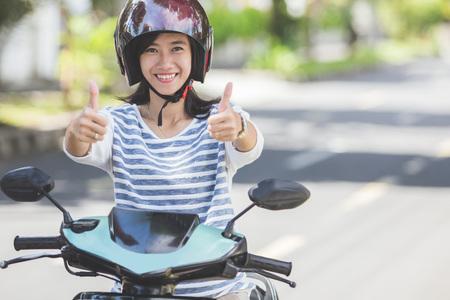 도시 거리에서 오토바이를 타고 엄지 손가락을 보여주는 행복 한 아시아 여자의 초상화