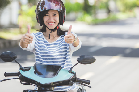 Portret van gelukkige Aziatische vrouw rijden op de motorfiets in de stad straat en duimen omhoog Stockfoto