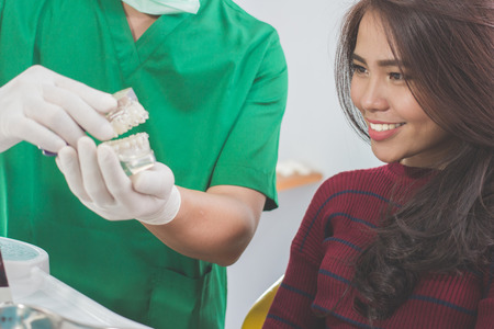 dentist showing dental jaw model to female patient in dentist's office photo