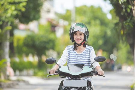 都市のオートバイの通りに乗って美しい魅力的なアジア女性 写真素材