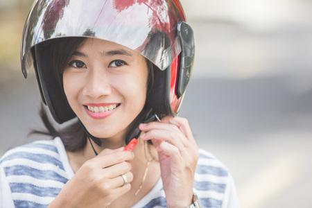 casco moto: mujer feliz la fijación de su casco de la moto en la calle de la ciudad Foto de archivo