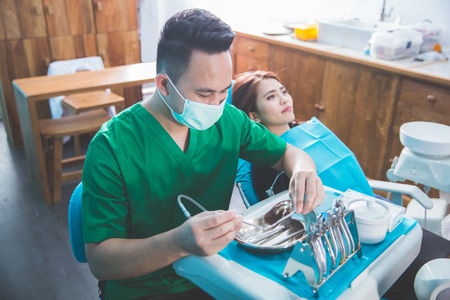 Portrait of a dentist who treats teeth of young woman patient photo