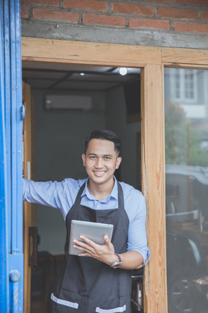 Confident young male with tablet standing in front of his business property