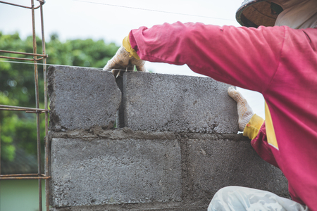 Close up of industrial bricklayer installing cement bricks on construction site