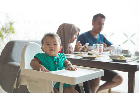 portrait of cute little girl sitting on a high chair. her parents in the background having a meal Stock Photo