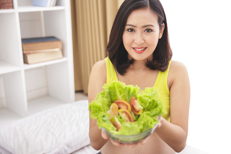 portrait of pregnant woman holding a bowl of fresh salad at bedroom Stock Photo