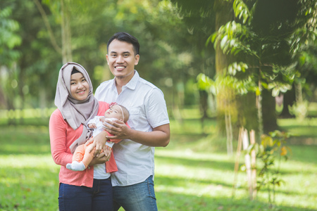 Portrait de famille heureuse asiatique avec nouveau-né dans le parc Banque d'images - 79995015