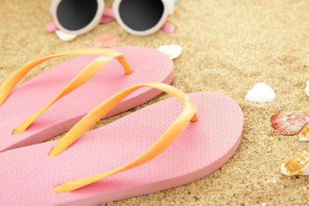 close up portrait of pink flipflops on beach sands