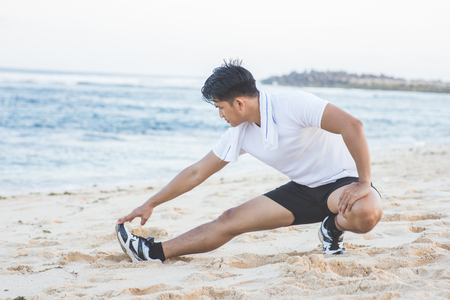 Fit man warming up doing lunges exercising during morning run at the beach