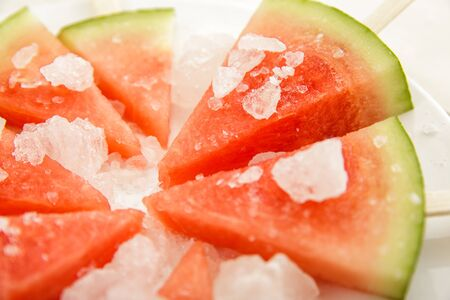 close up portrait of fresh cold watermelon popsicle on white plate Stock Photo
