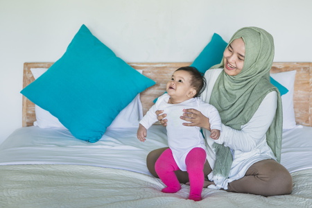 portrait of mother and her baby in the bed having fun Stock Photo