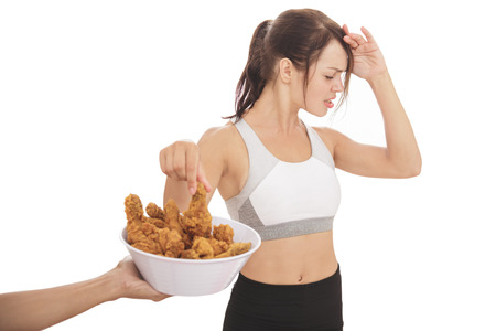 portrait of young sporty woman resisting the temptation of fried chicken isolated on white background Stock Photo