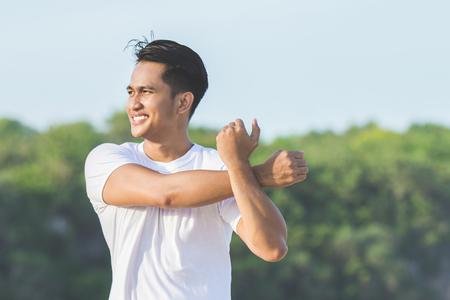 ハンサムなアジアの若い男性のビーチでジョギングする前に、のウォーミング アップ