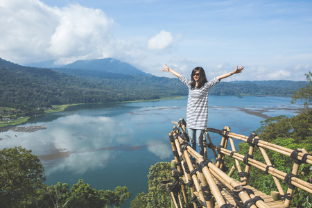 Carefree happy woman standing on top of mountain edge cliff enjoying sun on her face.Enjoying nature sunset.Freedom.Enjoyment.Relaxing in mountains