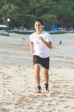 portrait of Handsome asian man running on the beach Stock Photo