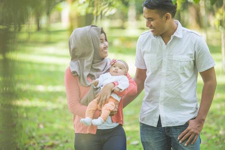 portrait de famille heureuse asiatique avec un bébé nouveau-né dans le parc
