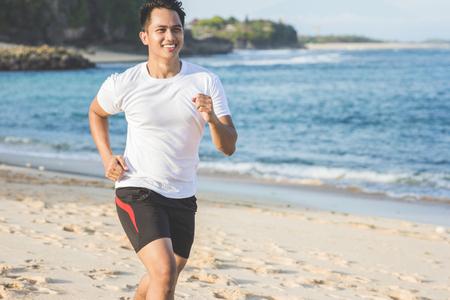 portret van de knappe Aziatische man loopt op het strand Stockfoto