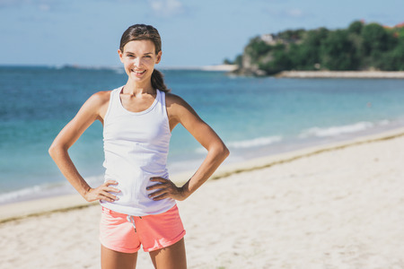 portrait of sporty woman with hands on her waist workout at the beach Stock Photo