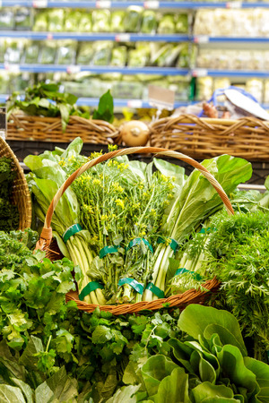 portrait of a basket of mustard greens at grocery Stock Photo