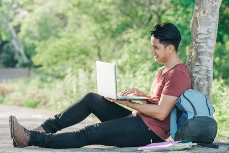 Junge männliche Student mit Laptop lächelnd beim Studium online unter dem Baum im Park
