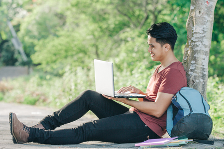 young male student with laptop smiling while studying online under the tree in the park