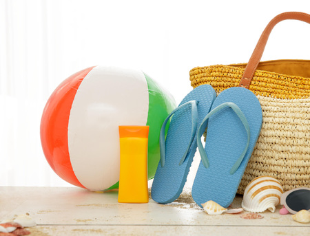 close op portrait of beach ball, sunblock, flipflops and bag on white wooden table isolated on white background