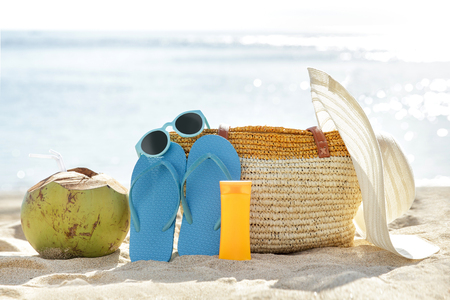 portrait of young coconut, flipflops, sunglasses, bag, sunblock, and hat on sand for summer vacation Stock Photo