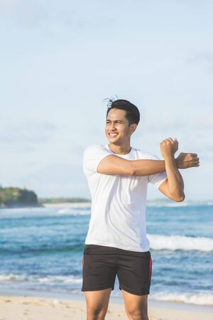 warming up: handsome asian athlete warming up before jogging at the beach