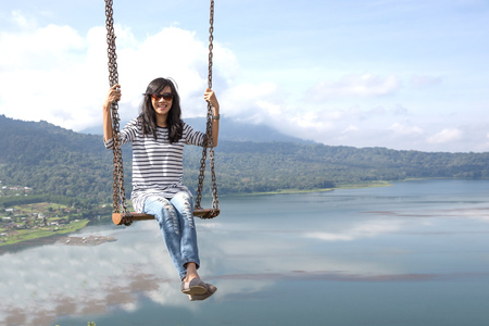 Carefree happy woman swinging on top of mountain edge cliff enjoying sun on her face.Enjoying nature sunset.Freedom.Enjoyment.Relaxing in mountains