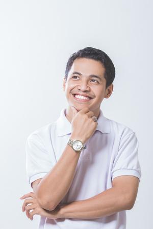 若い思考の男の肖像は、白で隔離 - 顔の近くに手でを検索します。 写真素材