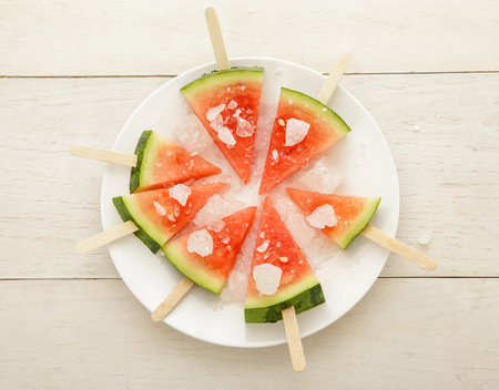 top view of fresh watermelon popsicle summer fruit dessert on white plate with white wooden background