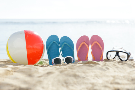 portrait of flipflops, beach ball, sunglasses, and snorkel on the sand