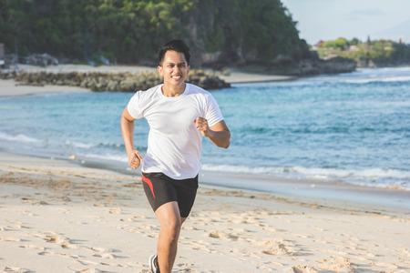 Portret van knappe Aziatische man die op het strand loopt Stockfoto