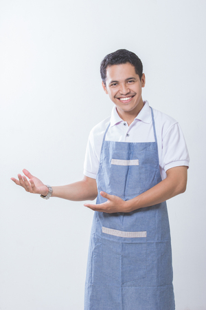 Small business shop owner. Apron man smiling proud and happy isolated on white background. Young entrepreneur asian male presenting copy space Archivio Fotografico