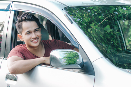 portrait of asian man in casual driving a car and looking at camera Imagens