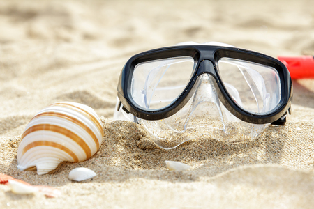 scuba goggles: close up portrait of mask and snorkel on the sand with seashells Stock Photo