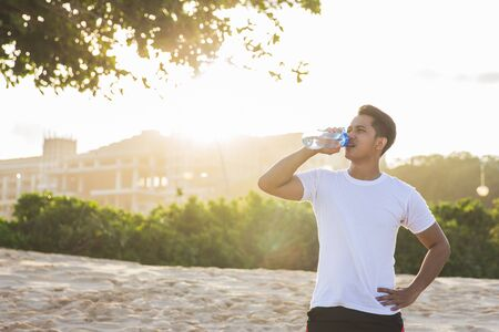 portrait of sport man drinking water from a bottle outdoor