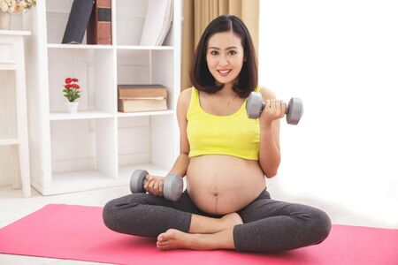 portrait of healthy pregnant woman exercising using dumbbells at home