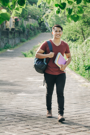 confident asian student walking in the park and holding a books