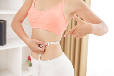 close up portrait of sporty woman measures her waist with measuring tape while pointing