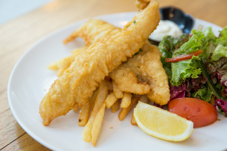 portrait of traditional British fish and chips with salads