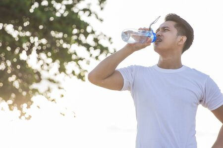 portrait of sport man drinking water from a bottle outdoor
