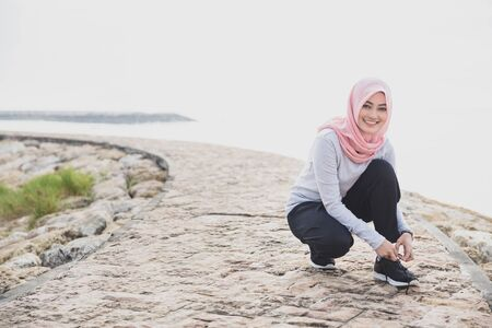 fit: portrait of sporty asian woman wearing hijab fixing the shoelaces during jogging with copy space Stock Photo