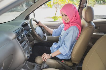 portrait of asian woman wearing hijab driving a car and shifting the gearshift